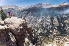 A young asian woman looks down into a deep granite gorge in the California mountains